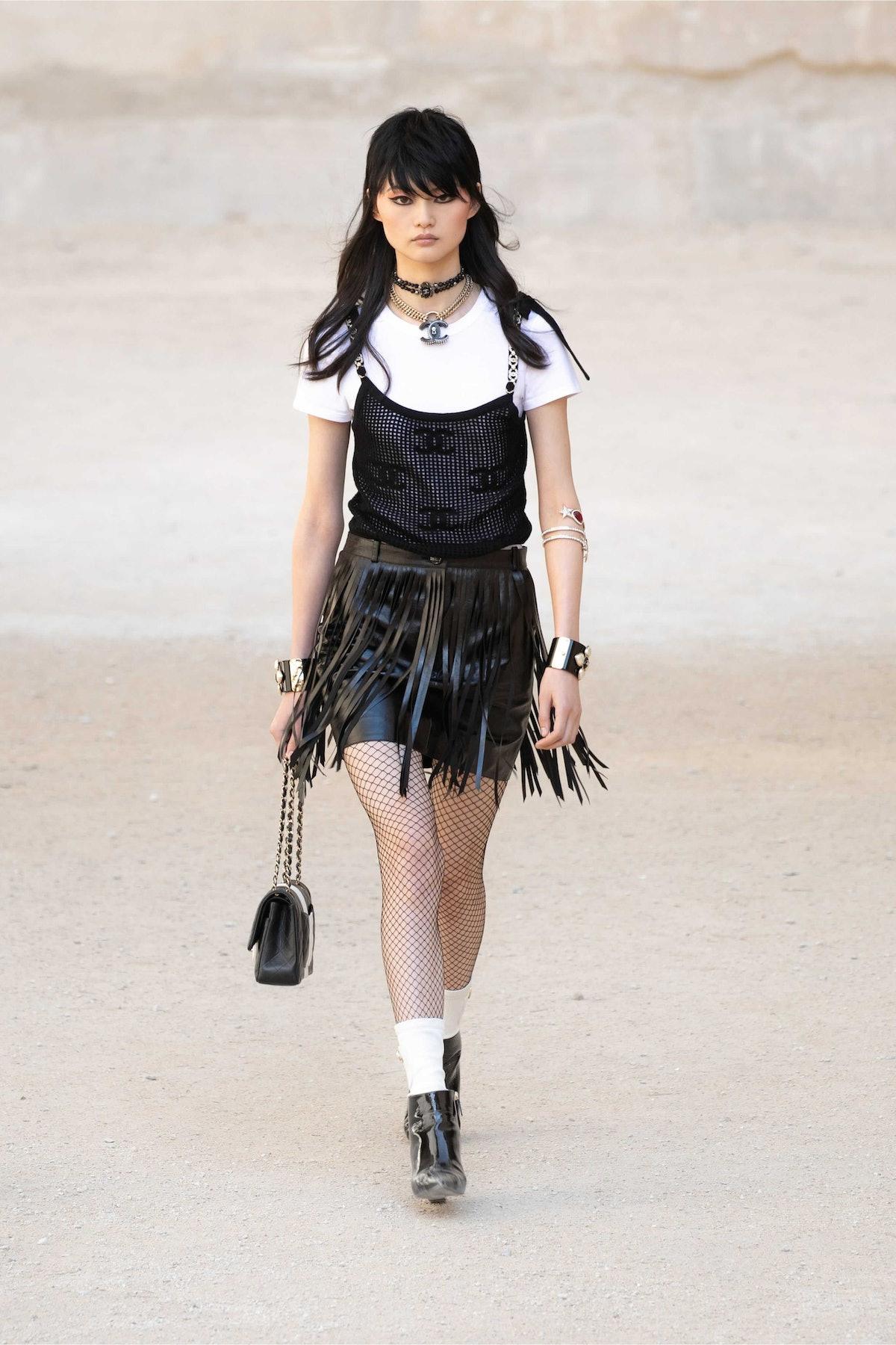 model in Chanel fringe skirt white tee and black tank top