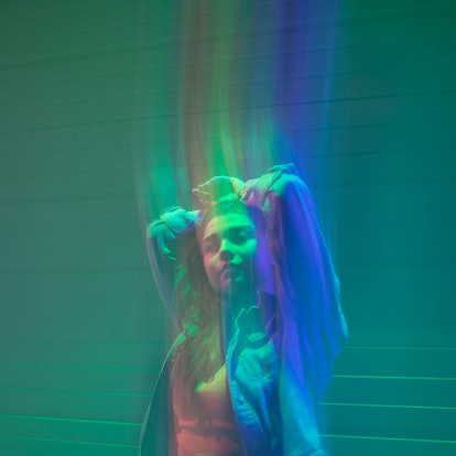 Young woman illuminated by a rainbow of colors during the May 2021 full blood moon.
