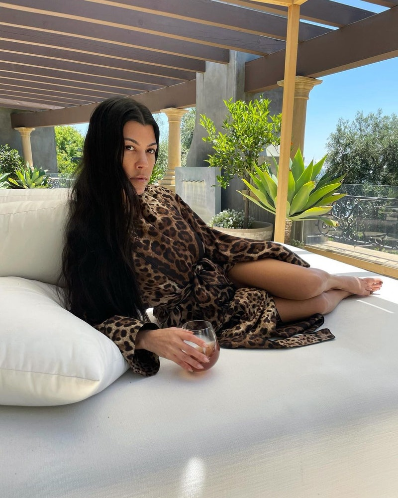 kourtney kardashian lounging on a white chair with a glass of collagen juice