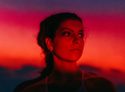 Young woman in neon red light during the May 2021 full blood moon, total lunar eclipse.