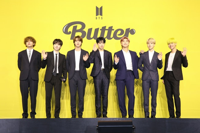 """A photo of BTS. All 7 members are in black suits and standing against a yellow """"Butter"""" press background, waving."""