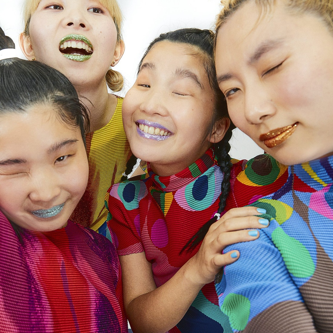 A photo of CHAI. The four members are wearing colorful tops, and all winking into the camera. They a...