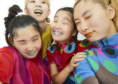 A photo of CHAI. The four members are wearing colorful tops, and all winking into the camera. They are wearing glittery make-up.