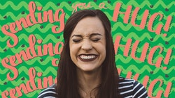"""Woman smiling in front of a Father's Day zoom background that says """"sending you a hug!"""""""