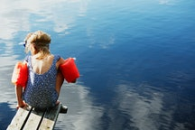 Child with swim floaties sits on dock over water