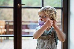 Young child putting on cloth face mask