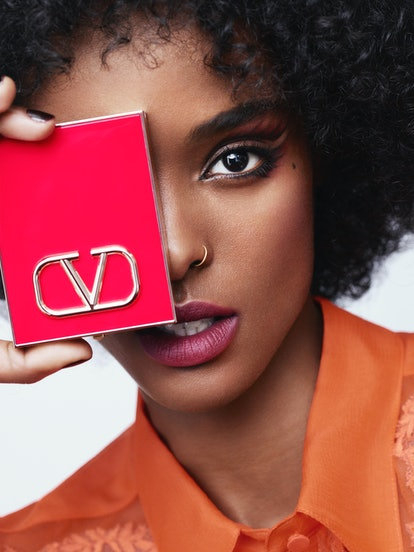 Model in Valentino makeup holding compact