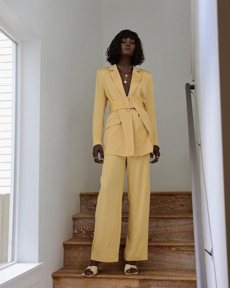 Model Amy Julliette Lefévre wears a yellow pantsuit.