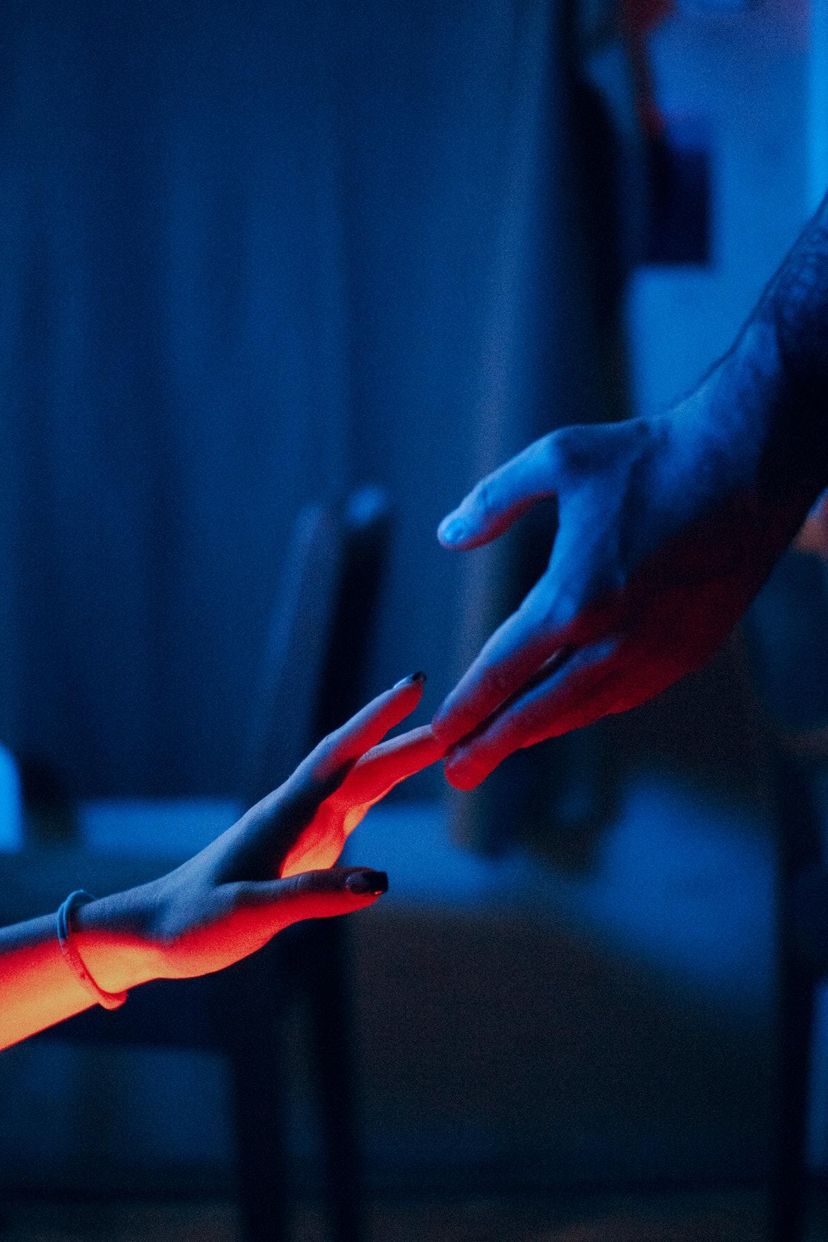 Couple touching hands amid Mercury retrograde spring 2021.