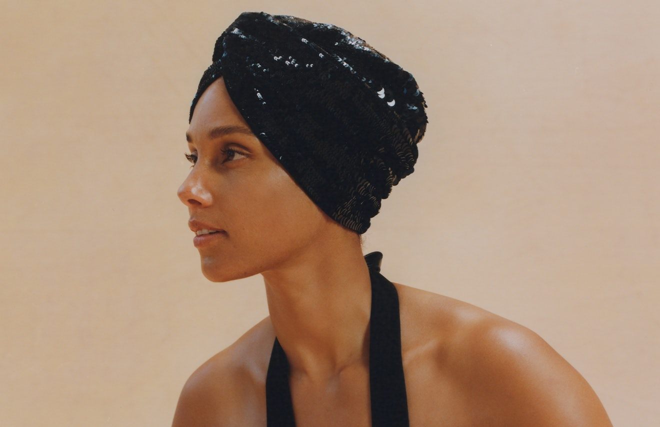 A close-up profile shot of Alicia Keys wearing a black Hermes jumpsuit. Keys is Bustle's May cover star.