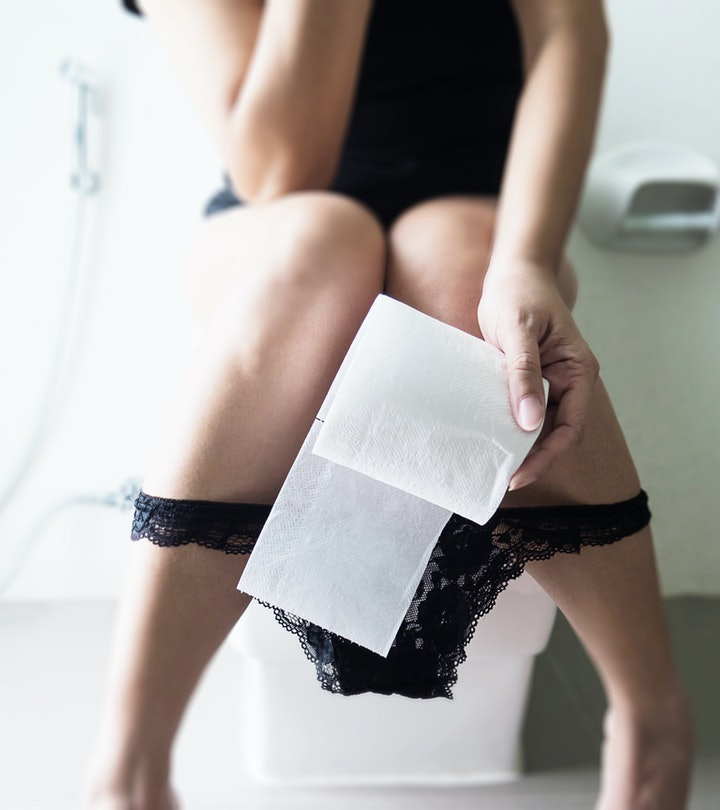 woman sitting on toilet with toilet paper in her hand