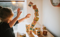 child knocking down blocks that spell out scallywag