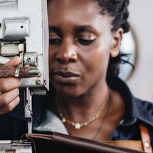 A woman at a sewing machine.