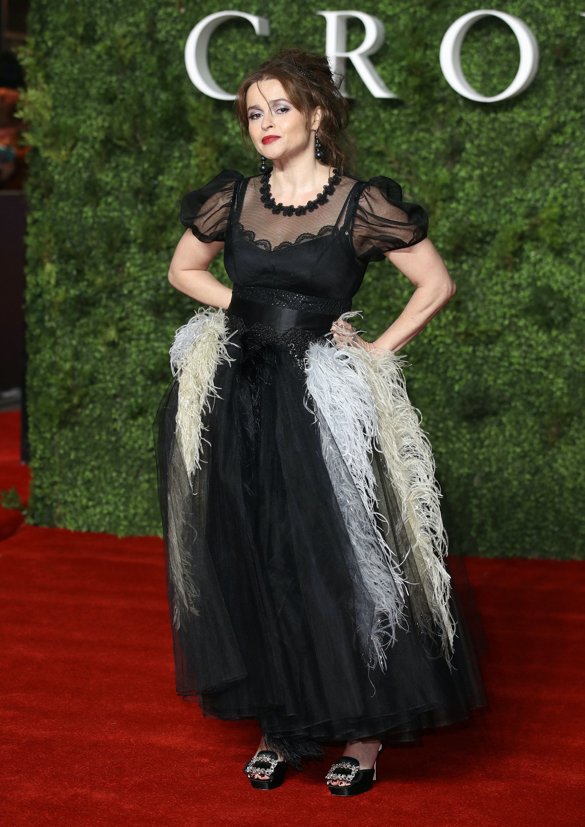 Helena on a red carpet The Crown in feathered gown