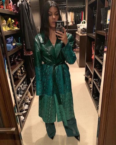 Kourtney Kardashian wearing a green snakeskin trench coat.
