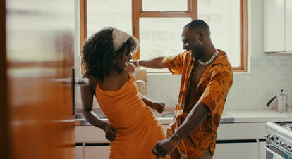 Young couple dancing in the kitchen on the most romantic day in June 2021.
