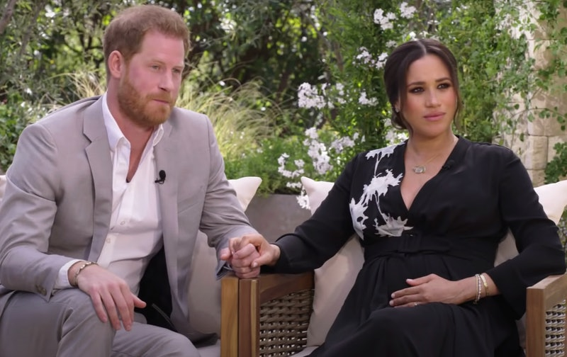 Harry and Meghan during their oprah interview sat against a backdrop of greenery, with harry wearing a grey suit and white shirt and meghan wearing a black dress