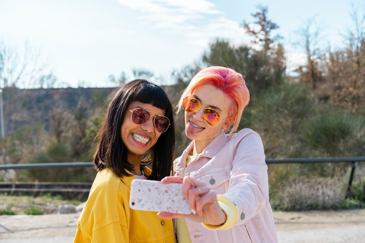 2 young friends taking a selfie on the best day in June 2021 for every zodiac sign.