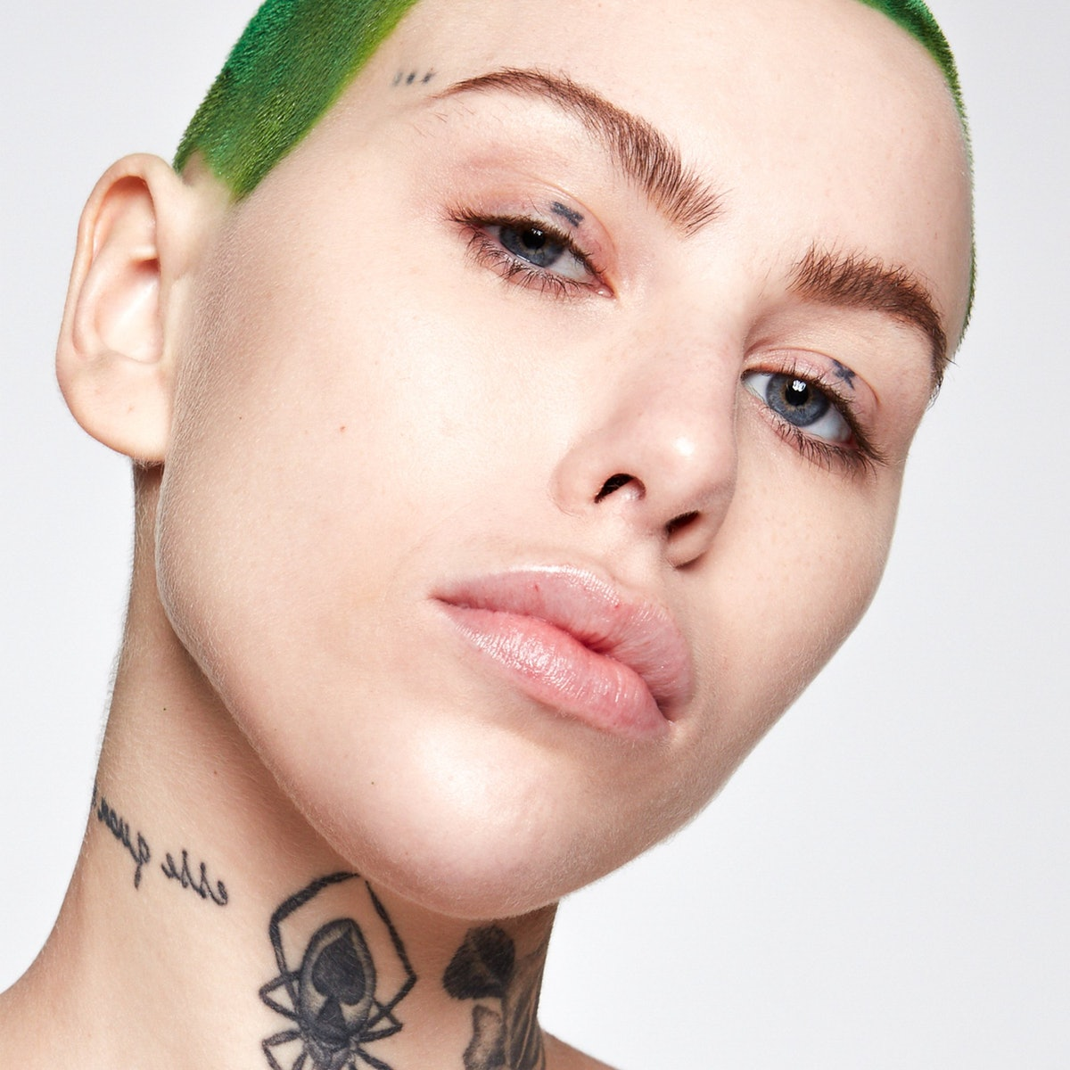A model with tattoos and green hair modeling Kosas Tinted Face Oil, one of several skin tints that are best for lightweight coverage.