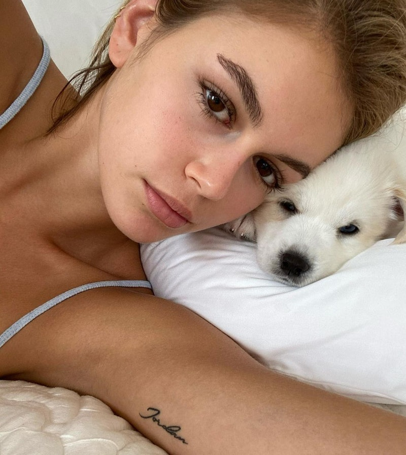 a selfie of kaia gerber and her white puppy