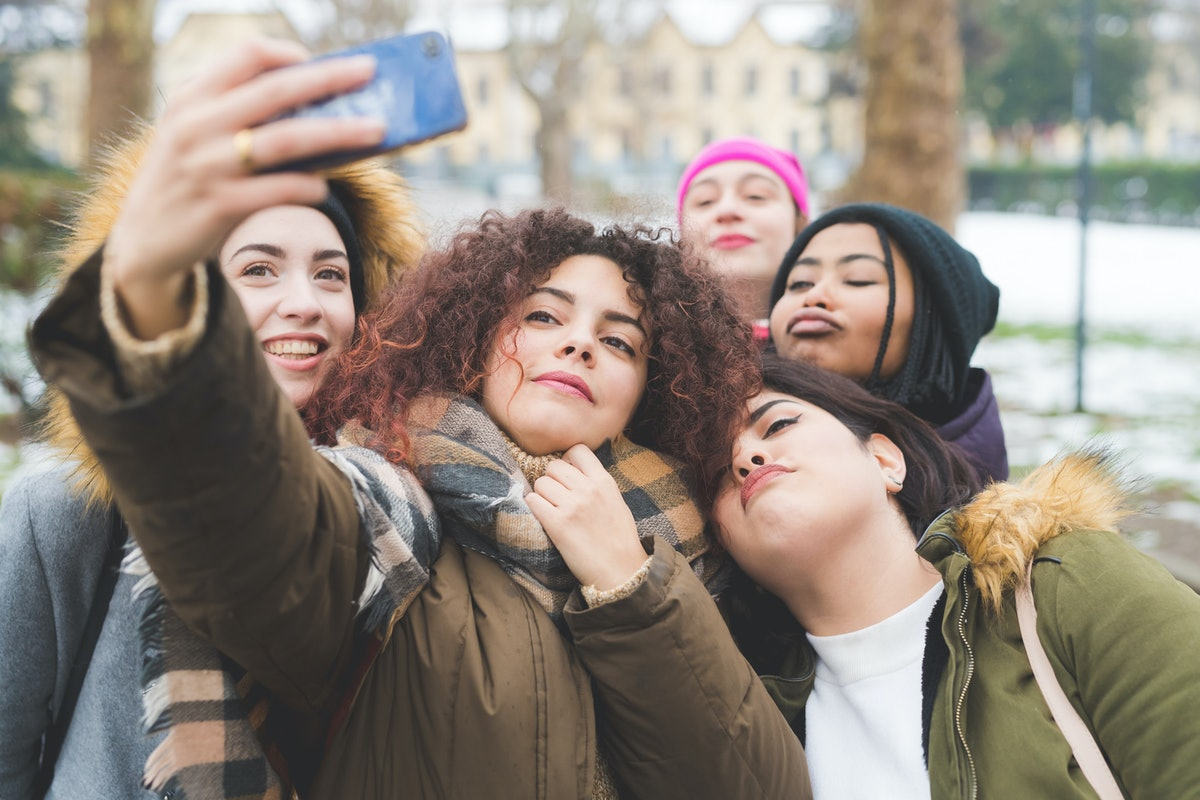 Group of 5 young women taking a selfie.