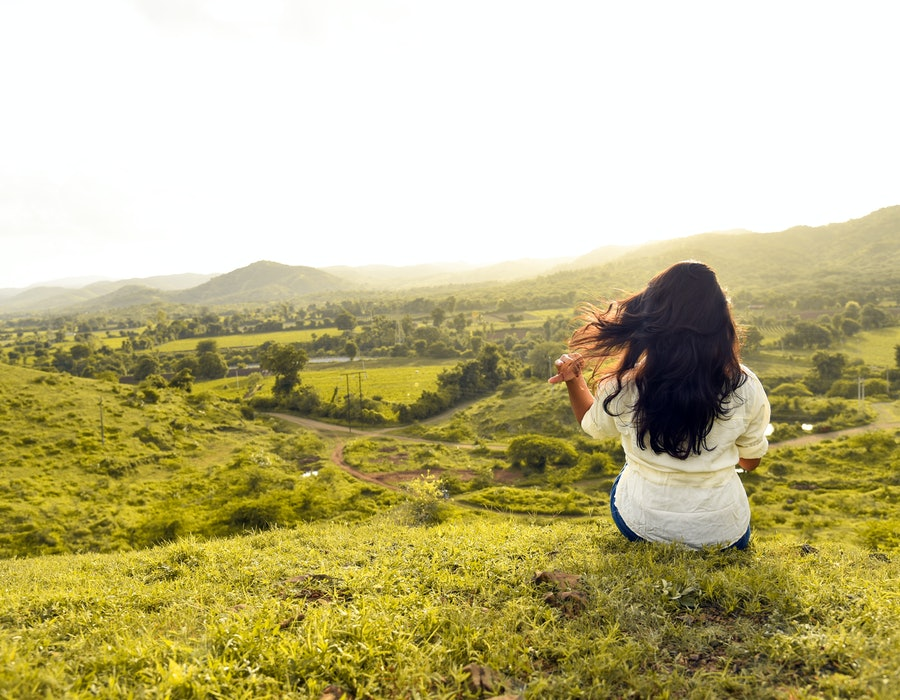 Woman sitting on a hill and staring out into a field.