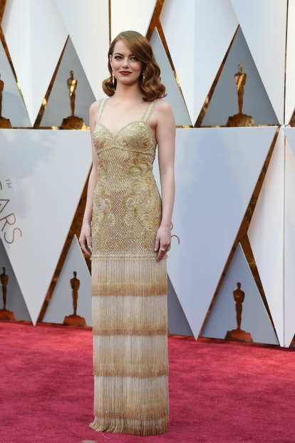 Stone at the Oscars red carpet in 2017 wearing a gold gown