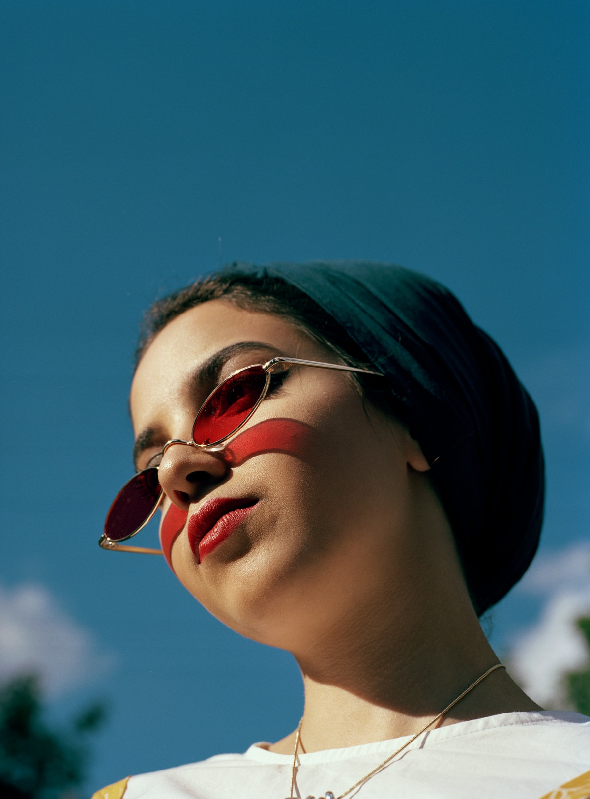 Young woman with red sunglasses during the week of May 31, 2021, waiting for her weekly horoscope.