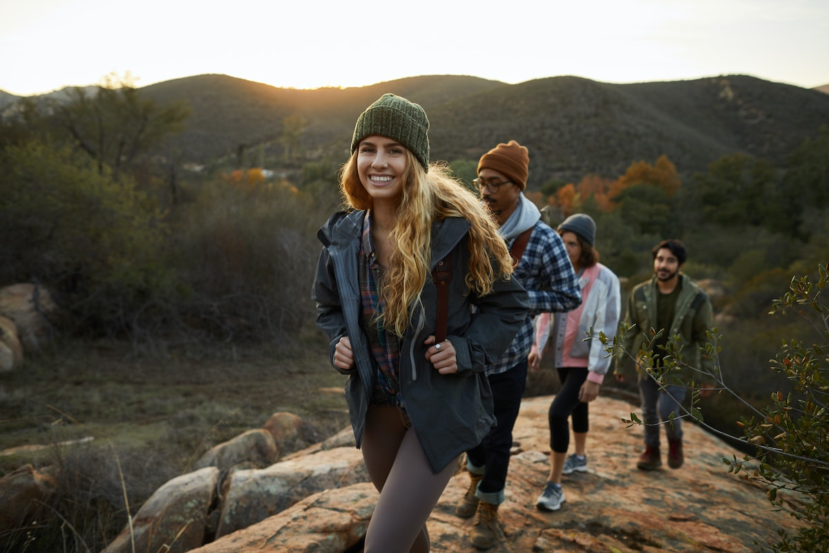 Young woman hiking with friends, preparing hiking captions, hiking instagram captions, and mountain puns.
