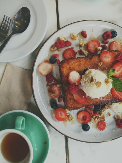 Plat with french toast topped with ice cream, berries, and granola crumbles