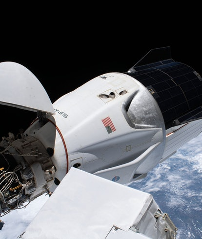 The SpaceX Crew Dragon spacecraft, with its nose cone open, is pictured docked to the Harmony module's forward international docking adapter.