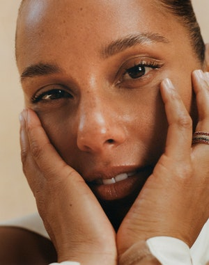 A closeup beauty shot of Alicia Keys touching her face as she poses for Bustle's cover.