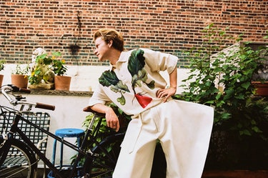 Gem chef Flynn McGarry wears white pants and a white shirt with a vegetable on it while standing near a bicycle outside.