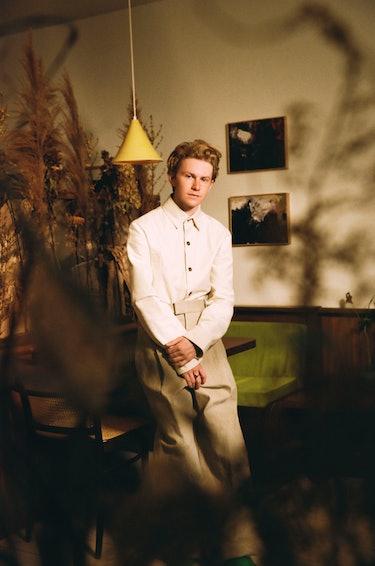Gem chef Flynn McGarry wears Bottega Veneta while posing inside against a table for Bustle's food issue.