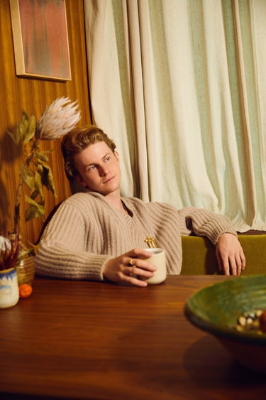 Gem chef Flynn McGarry wears a tan Prada sweater and sits at a table holding a coffee mug.