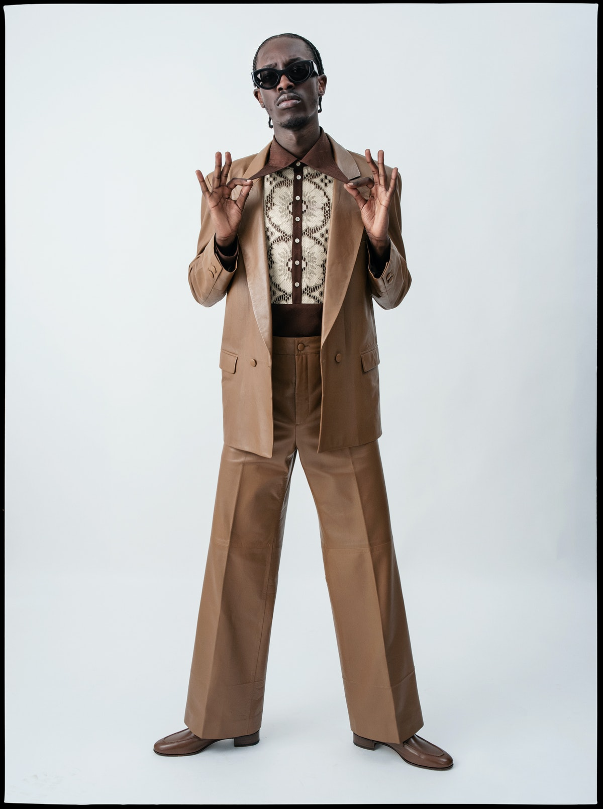 Unknown T wears a Gucci blazer, shirt, pants, and shoes.
