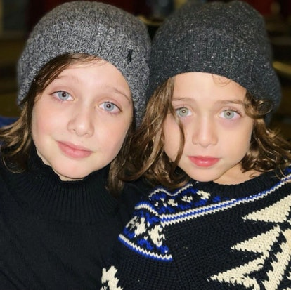 two kids with winter hats on, looking chic