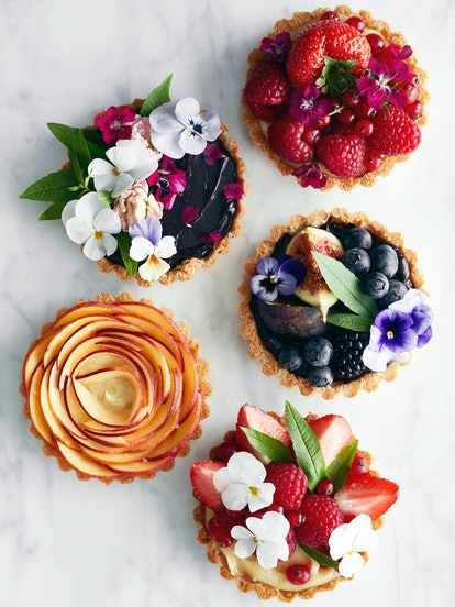 Five fruit tarts in various flavors; garnished with fresh flowers