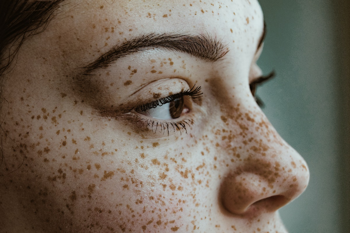 Young woman closeup on brows, freckles, and lashes