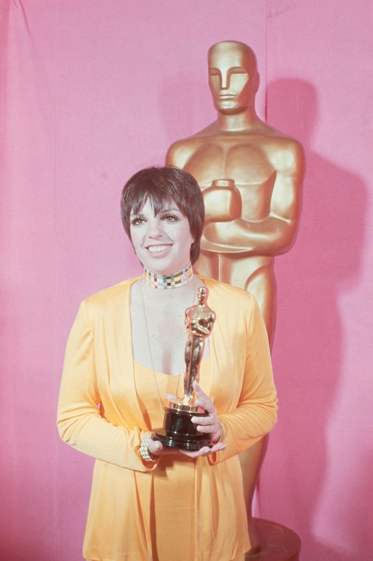 Liza wears a gold ensemble, holds Oscar