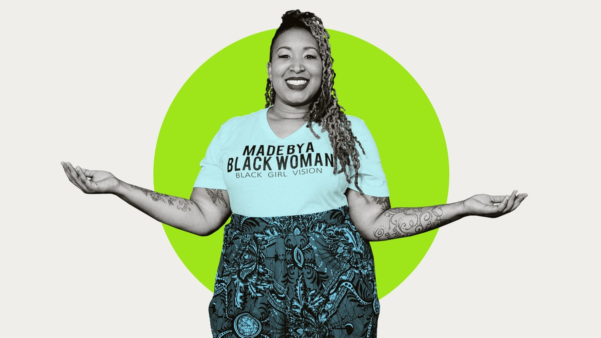 """Entrepreneur Shelly Bell, wearing a t-shirt with """"Made By A Black Woman : Black Girl Vision"""", smiles and stands with arms outstretched to either side in front of an abstract green and white background"""