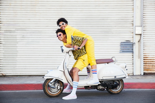 Young woman spoiled by her boyfriend on scooter, per her zodiac sign