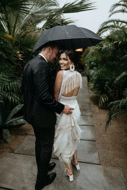 Groom gazing at bride, who is wearing circular raffia earrings.