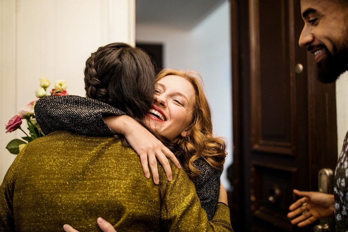 Spoiled young woman hugging her friend, per her zodiac sign