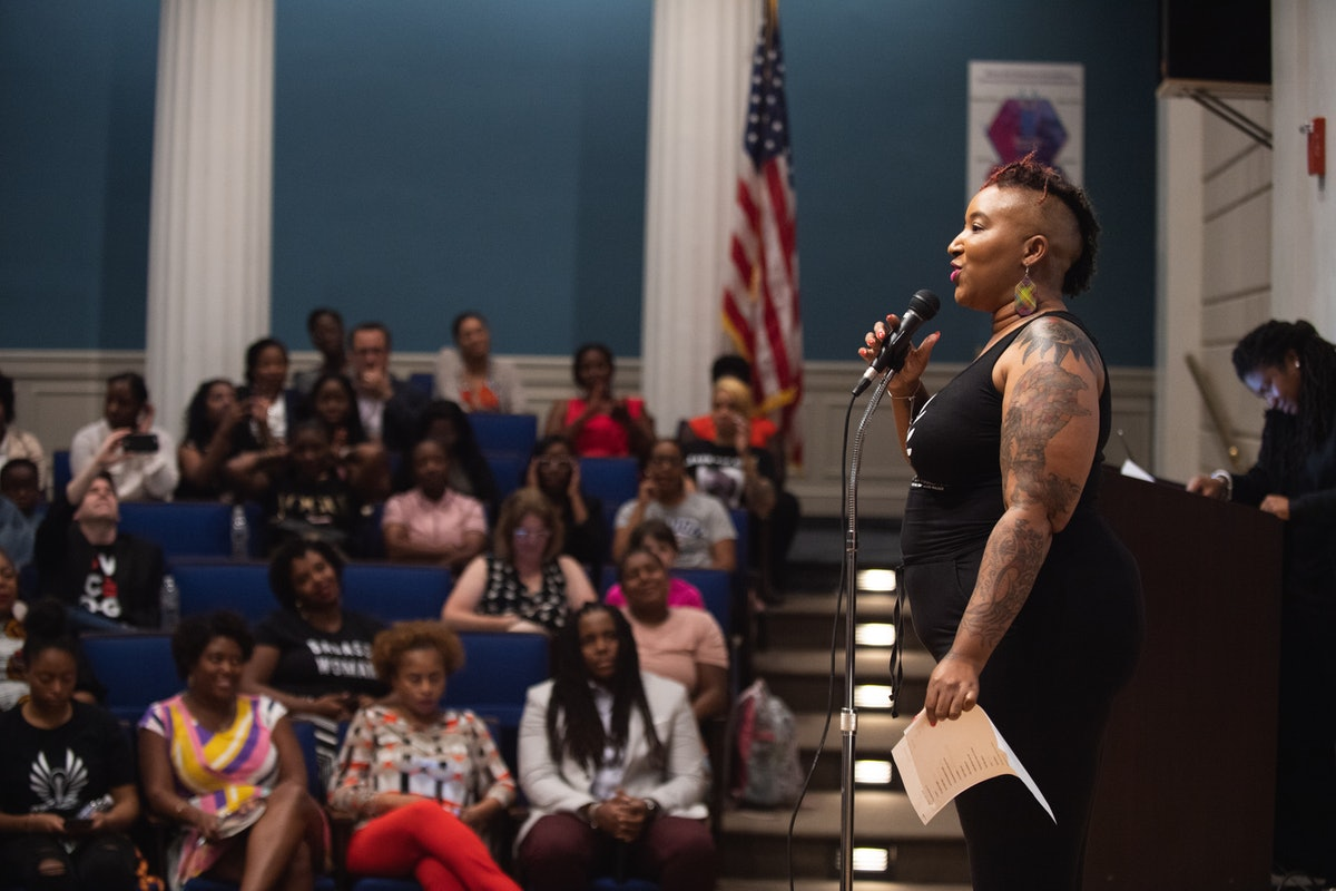 Entrepreneur Shelly Bell stands in front of a microphone in an auditorium, speaking to a crowd of mostly Black and brown women