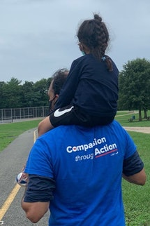 Viewed from the back, we see Qasim Rashid and his daughter, Hannah, on his shoulders.