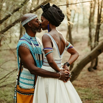 Groom and bride kissing, bride is wearing colorful beaded Xhosa jewelry.