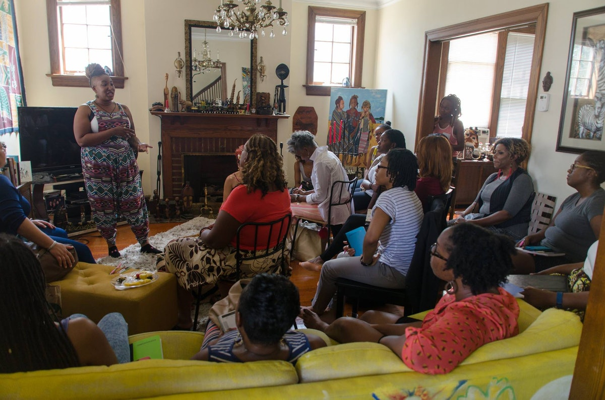 Entrepreneur Shelly Bell, wearing  multicolored jumpsuit, stands to speak to a gathering of Black and brown women in a suburban living room. The gathering is casual, but crowded: people have pulled in chairs and lean on the door to listen as she speaks