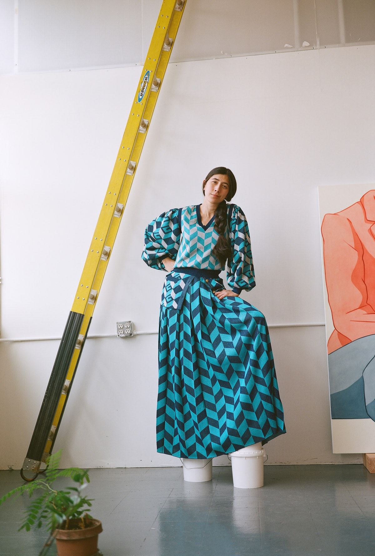 Haldeman wears a Gucci blouse, vest, and skirt; her own shoes in her studio.