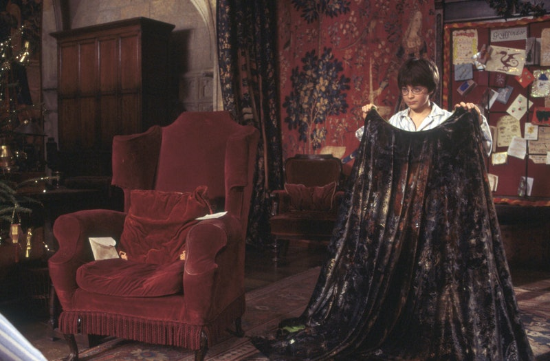 Harry Potter holding his invisibility cloak